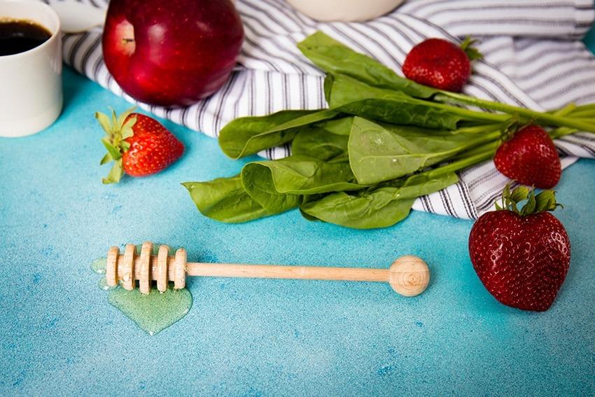 frischer Salat mit Obst und Honiglöffel