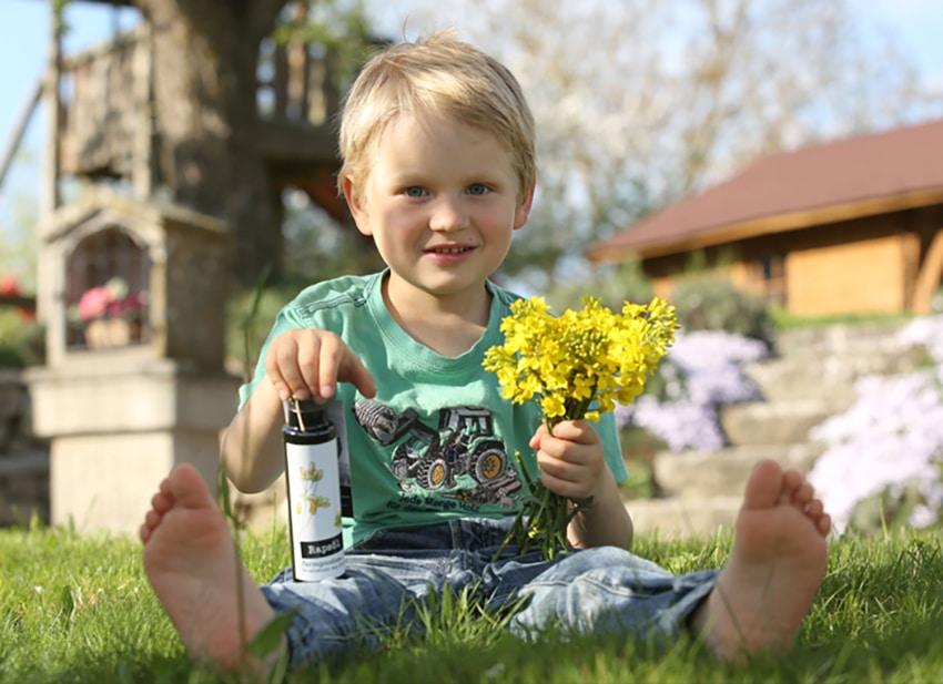 Kind sitzt auf der Wiese mit Öl der Farmgoodies