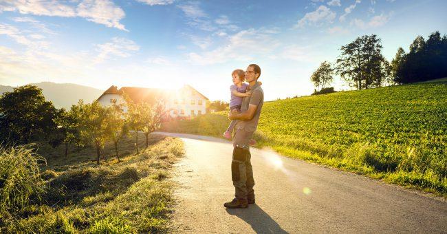 Mann mit seinem Jungen auf dem Arm bei Sonnenuntergang auf einer Straße