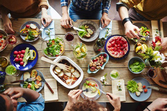 Menschen an einem reich gedeckten Tisch von oben fotografiert