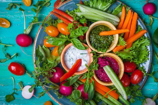 Teller mit verschiedenstem rohen Gemüse und 3 Dips auf türkisem Untergrund