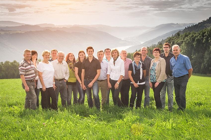 Team von Sauwald Erdäpfel auf einer Wiese mit Bergen im Hintergrund