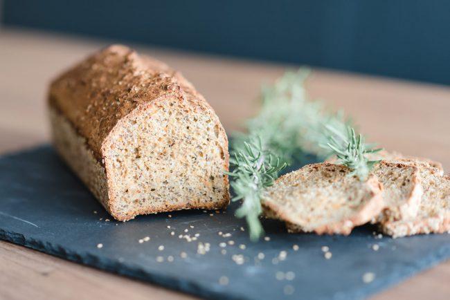 aufgeschnittenes Brot auf einer Schieferplatte mit Rosmarin