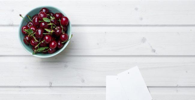 Kirschen in Schüssel auf weißem Holzuntergrund