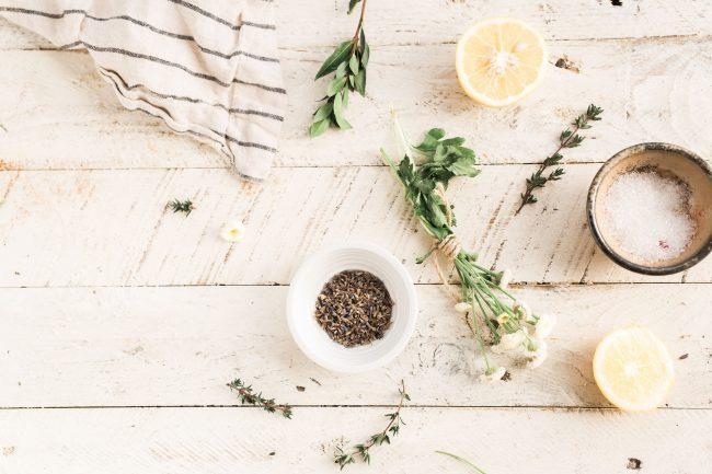 Kräuter, Salz, Pfeffer und Zitrone auf einem Holzuntergrund